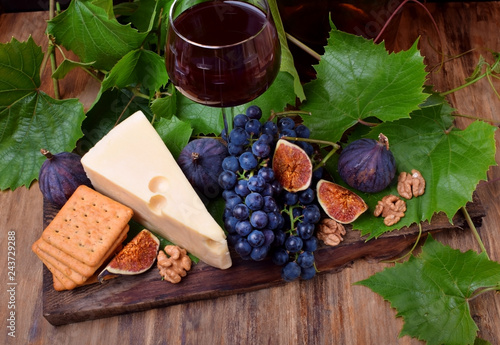 In de dag Voorgerecht Red wine in a glass surrounded by the appetizers: Maasdam cheese, figs, walnuts and a bunch of Isabella grapes on a wooden board