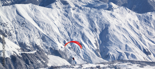 Panoramic view on paragliding at snowy mountains over ski resort at sunny winter day