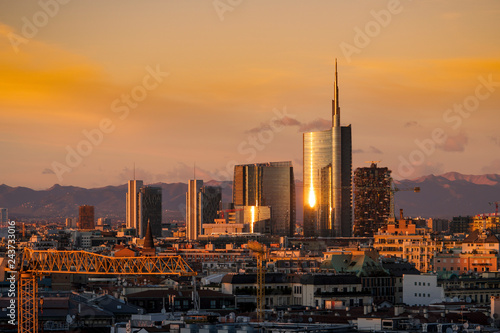 Photo sur Aluminium Noir Milan skyline at sunset with modern skyscrapers in Porta Nuova business district in Italy. Panoramic view of Milano city. The mountain range of the Lombardy Alps in the background.