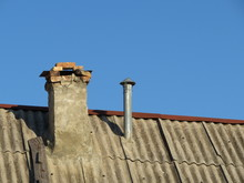 Old And New Chimney On The Old Slate Roof Of The House Isolated On Clear Blue Sky Background. Stove Heating Concept
