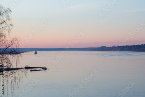 Foto  Peaceful spring landscape at sunset on the river with ship and forest in the background