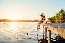 Beautiful Girl In A Hat At Sunset Catches Fish On The Pier At The Lake.