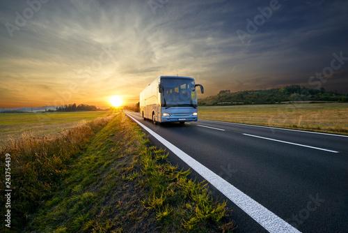 Foto  Bus traveling on the asphalt road in rural landscape at sunset