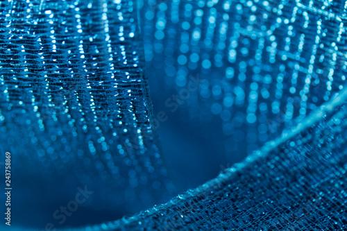 Vibrant blue metallic ribbon macro abstract background with bokeh