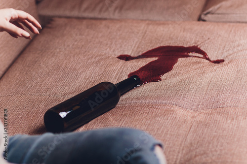 Obraz Red wine spilled on a brown couch sofa. dark bottle of red wine dropped - fototapety do salonu