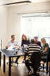 Designers discussing work together around an office table