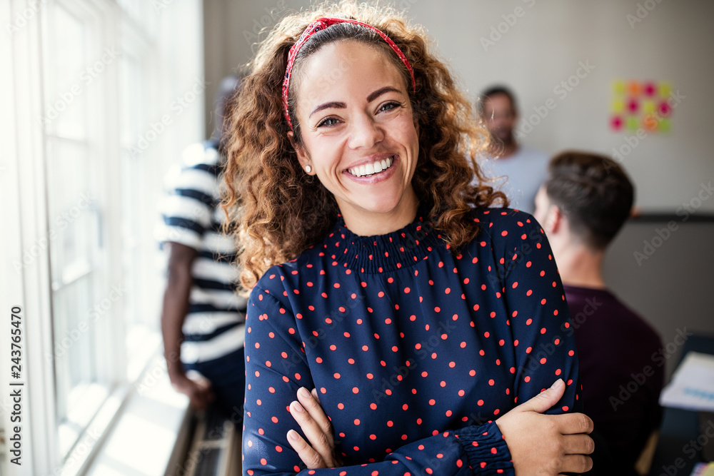 Fototapeta Smiling female designer standing in an modern office