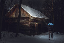 Man (photographer) Standing In Front Of The Abadoned And Creepy Cottage In Forest In Winter. Man On Expedition Is Shinning With Flash Light On Dark Wooden Bothy In Snow Storm In Mountains.