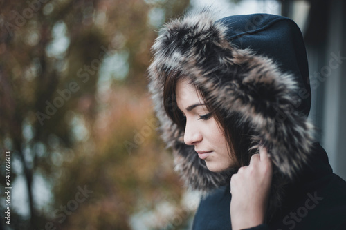 Fotografía  Close up autumn portrait of young and cute woman in blue jacket with furry hood on her head