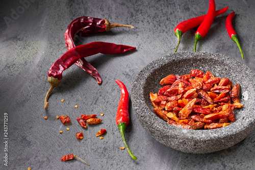 Printed kitchen splashbacks Spices Closeup on fresh hot chili peppers on dark textured table and dry ones in stone bowl