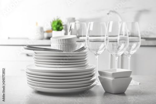 Photo  Set of clean dishes and cutlery on table in kitchen