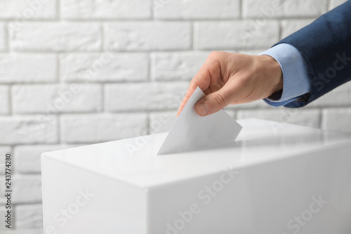 Poster Historisch geb. Man putting his vote into ballot box against brick wall, closeup