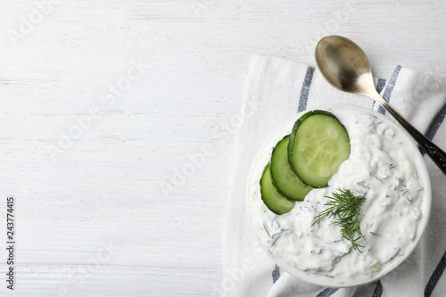Photo Cucumber sauce, spoon and space for text on wooden background, flat lay