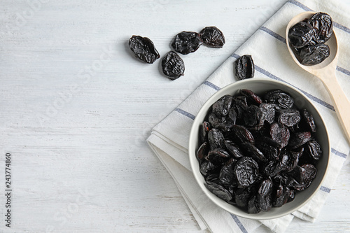 Bowl and spoon of sweet dried plums on table, top view with space for text. Healthy fruit