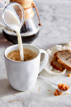 Pouring Milk In Coffee With Banana Bread