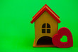Leinwanddruck Bild - wooden house with a red roof on a green background.conceptual photo