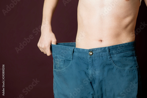 Fotografía  person show weight loss by wear large size trousers b