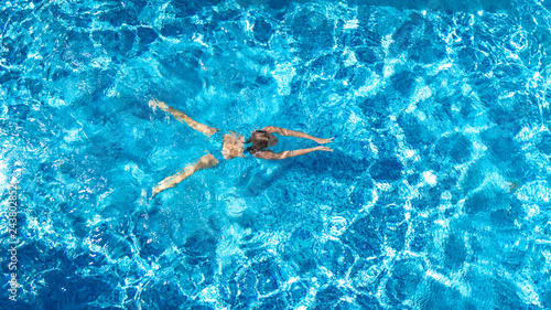 Fotobehang Ontspanning Active girl in swimming pool aerial drone view from above, young woman swims in blue water, tropical vacation, holiday on resort concept