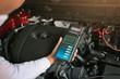 Man inspection holding Battery Capacity Tester Voltmeter.