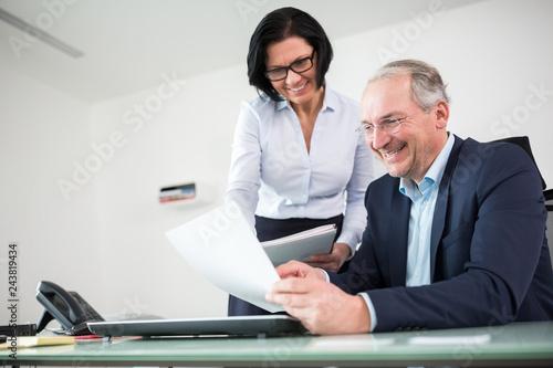 Geschäftsführer und Kollegin mit Akte Canvas Print
