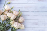 Pink Eustoma flowers on light wooden background. Flat lay, top view.