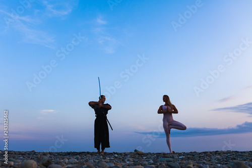Fotografie, Obraz  silhouette of Aikido fighter in traditional costume with sword and woman yoga in