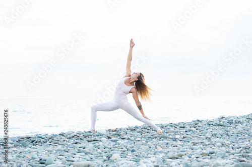 Fotografie, Obraz  Flexible and athletic slim young female athlete blonde in a tight white suit mak