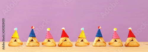 Purim celebration concept (jewish carnival holiday). Traditional hamantaschen cookies with cute clown hats over wooden table and purple background. Banner.