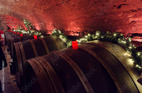 Fotomural Wine barrels in an old wine cellar with red candles and fairy lights