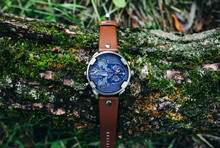 Big Elegant Men's Watch Is Lying On The Tree With Green Moss Outdoors. Stylish Fashion Accessories In The Nature.