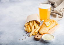 Traditional British Fish And Chips With Tartar Sauce Abd Glass Of Craft Lager Beer On Chopping Board On White Stone Table Background. Space For Text