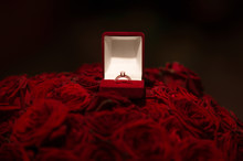 Front View Of Beautiful Wedding Ring With Precious Stone In Red Velvet Gift Box On Red Roses Background. For Present And Marriage Proposal.