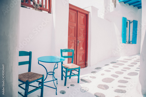 Poster Historisch geb. Blue chairs and table on street of typical greek traditional village with white houses on Mykonos Island, Greece, Europe
