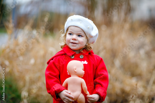 761fd543e Outdoor portrait of little cute toddler girl in red coat and white fashion  hat barret with ...