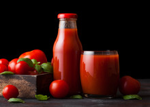 Bottle And Glass Of Fresh Organic Tomato Juice With Fresh Raw Tomatoes In Box On Stone Kitchen Background On Black