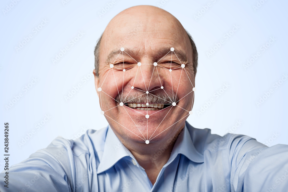 Fototapety, obrazy: Elderly man holding a smartphone passing through facial recognition.