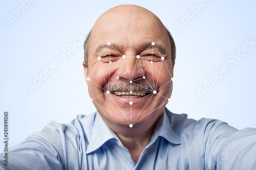Fotografie, Tablou  Elderly man holding a smartphone passing through facial recognition