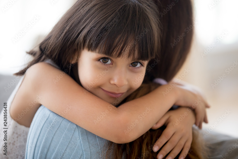 Fototapeta Adorable little daughter hugging mother looking at camera, mum and happy cute girl cuddling, smiling sincere child embracing mommy, childrens day, adoption, sweet kids love for mom concept, portrait