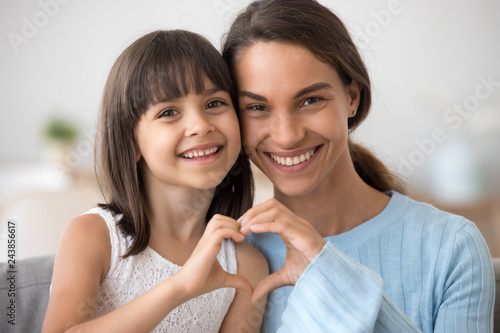 Cute little daughter and happy mother join hands in shape of heart as concept of mom and child love care support, smiling mum and her kid girl looking at camera posing together for headshot portrait