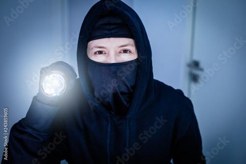 Photo  Porträt eines Einbrechers mit Sturmmaske und leuchtender Taschenlampe im dunklen
