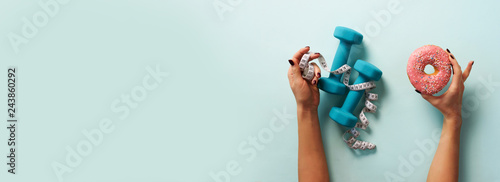 Obraz Female hand holding sweet donut, measuring tape, dumbbells over blue background. Top view, flat lay. Weight lost, sport, fitness, diet concept. Banner with copy space. - fototapety do salonu
