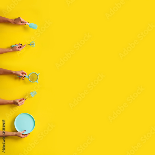 Photo  Hands holding kitchen tools holding kitchen tools, sieve, rolling pin, bowl, sieve, brush, whisk, spatula for baking and cooking on yellow background
