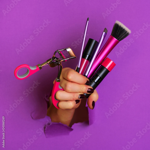 Woman hand with professional cosmetic tools for make up: brushes, mascara, lipstick, eyelash curler on violet background Canvas Print