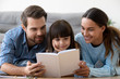 Leinwandbild Motiv Happy mom and dad with little cute daughter holding reading book, smiling mother father and kid girl having fun playing at home spending time together, friendly parents and child readers concept