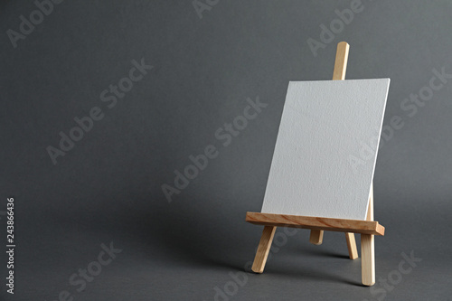 Photo  Wooden easel with blank canvas board on dark background, space for text