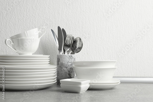 Staande foto Historisch geb. Set of clean dishes and cutlery on table near light wall. Space for text