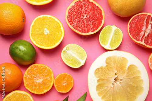 Different citrus fruits on color background, top view