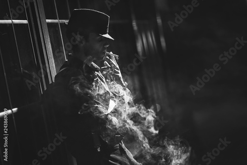 Tela  A man with a cigarette in a hat and a raincoat on the street of a night city