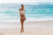 Beautiful tanned girl standing on beach with white sand and blue ocean