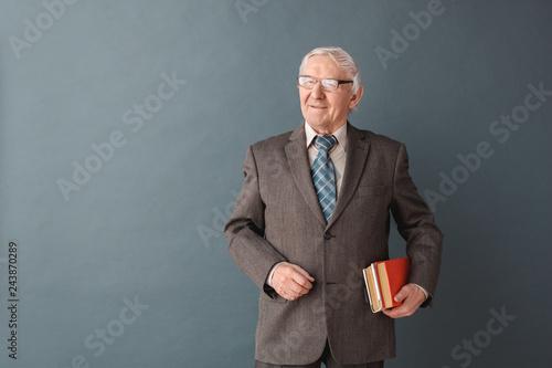 Fotografía  Senior man teacher wearing glasses studio standing isolated on gray holding book